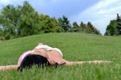 Moça que relaxa na grama em um parque imagens de stock royalty free
