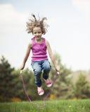Moça que salta no parque Fotos de Stock