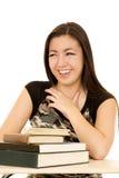Moça que senta-se atrás de uma pilha do riso dos livros Fotos de Stock