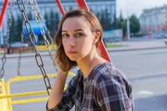Moça que senta-se em um balanço na cidade foto de stock royalty free