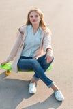 Moça que senta-se em um skate Fotografia de Stock