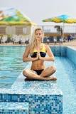 Moça que senta-se fora pela associação e que faz exercícios de Imagem de Stock Royalty Free