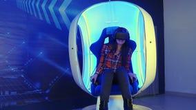 Moça que senta-se na atração da realidade virtual e que sente assustador vídeos de arquivo
