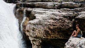 Moça que senta-se na borda de um penhasco e que olha a cachoeira Imagem de Stock