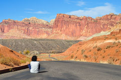 Moça que senta-se na estrada Fotos de Stock Royalty Free