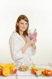 Moça que senta-se na mesa de cozinha, bebendo um milk shake da vitamina Fotos de Stock Royalty Free