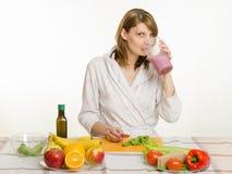 Moça que senta-se na mesa de cozinha, bebendo um milk shake do fruto de um grande copo Imagens de Stock