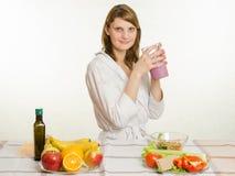 Moça que senta-se na mesa de cozinha com um milk shake do fruto à disposição Imagem de Stock Royalty Free