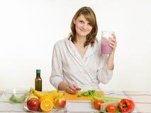 Moça que senta-se na mesa de cozinha e nas posses um o vidro grande do cocktail Fotografia de Stock