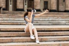 A moça que senta-se nas escadas, perto da universidade, está na realidade virtual, em VR Foto de Stock