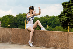 A moça que senta-se nas escadas, perto da universidade, está na realidade virtual, em VR Foto de Stock Royalty Free