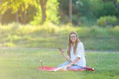 Moça que senta-se no parque, sorrindo e trabalhando em seu portátil, escutando a música imagens de stock