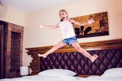 Moça que tem o divertimento que salta na cama no quarto imagem de stock