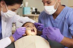 Moça que tem a verificação acima na cirurgia dos dentistas imagem de stock