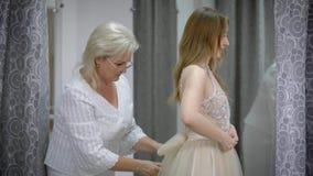 Moça que tenta no vestido com ajuda da costureira na loja do alfaiate filme