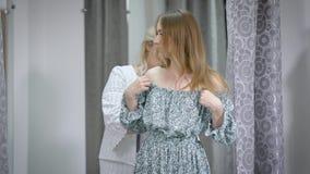 Moça que tenta no vestido novo na sala de estar com ajuda do alfaiate vídeos de arquivo