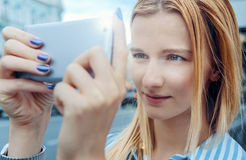 Moça que toma imagens no smartphone, dia, exterior na cidade Imagens de Stock