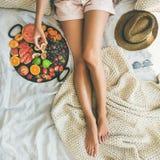 Moça que toma o figo da bandeja completamente de frutos frescos Fotos de Stock Royalty Free