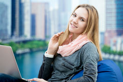 Moça que usa o portátil na poltrona confortável com a cidade grande no b Foto de Stock