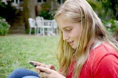 Moça que usa um telefone celular Foto de Stock Royalty Free