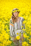 Moça que veste a blusa tradicional romena que levanta no campo do canola, tiro exterior Retrato do louro bonito com grinalda Imagem de Stock Royalty Free