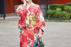 Moça que veste o quimono japonês que está na frente do templo de Sensoji no Tóquio, Japão O quimono é um vestuário tradicional ja Imagens de Stock Royalty Free