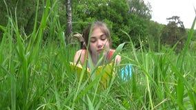 Moça relaxado que lê o livro no campo Encontro adolescente bonito na grama Tiro das imagens de vídeo HD da estática video estoque