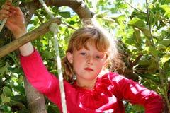 Moça séria na árvore Fotos de Stock Royalty Free