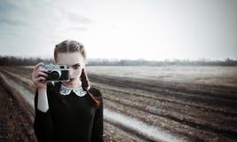 Moça séria que fotografa pela câmera velha do filme Retrato exterior no campo Foto de Stock