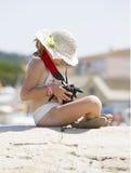 A moça senta-se com sua câmera Imagem de Stock Royalty Free
