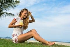 A moça senta-se em uma grama no país tropical da ilha Samui, o batido das bebidas da menina Foto de Stock