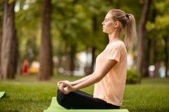 A moça senta-se na posição dos lótus com os olhos de fechamento que fazem exercícios com outras meninas sobre a grama verde no pa fotos de stock