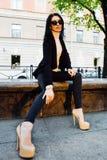 A moça senta-se na rua Imagem de Stock