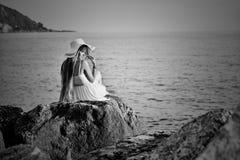 A moça senta-se para trás na pedra do mar Fotografia de Stock Royalty Free