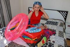 A moça senta-se perto da mala de viagem Menina ao lado da mala de viagem enchida em demasia Preparar-se para viajar Imagem de Stock Royalty Free