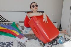 A moça senta-se perto da mala de viagem Menina ao lado da mala de viagem enchida em demasia Preparar-se para viajar Fotografia de Stock Royalty Free