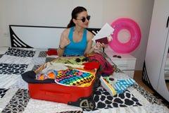 A moça senta-se perto da mala de viagem Menina ao lado da mala de viagem enchida em demasia Preparar-se para viajar Foto de Stock Royalty Free
