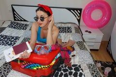 A moça senta-se perto da mala de viagem Menina ao lado da mala de viagem enchida em demasia Preparar-se para viajar Fotografia de Stock