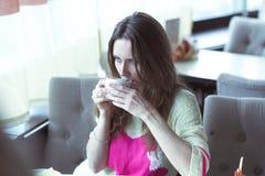 Moça, sentando-se em um café com xícara de café Imagem de Stock Royalty Free