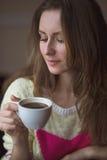 Moça, sentando-se em um café com xícara de café Foto de Stock