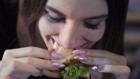 A moça 'sexy' come o sedvich Close-up O conceito da sociedade rápida do petisco e da obesidade Alimento para o freelancer filme