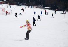 Moça sob a forma de um esqui abaixo da montanha em um snowboard Fotografia de Stock Royalty Free