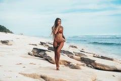 Moça tattooed 'sexy' no roupa de banho vermelho que levanta na praia Mulher loura bonita com o cabelo longo que relaxa no Imagem de Stock Royalty Free