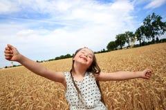 A moça tem o divertimento no campo de trigo Imagens de Stock
