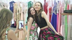 A moça toma imagens de suas amigas na câmera do telefone celular em um shopping da sala de mudança video estoque