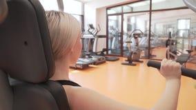 A moça treina os músculos das mãos em um simulador no vídeo da metragem do estoque do gym filme
