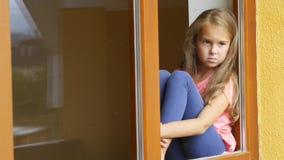 Moça triste que olha através de uma janela em casa vídeos de arquivo