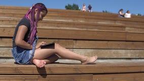 A moça usa uma tabuleta que senta-se em um banco de parque Movimento lento filme