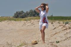 A moça vai com os pés descalços na areia fotos de stock royalty free