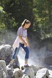 A moça vai nas rochas por um rio Fotografia de Stock